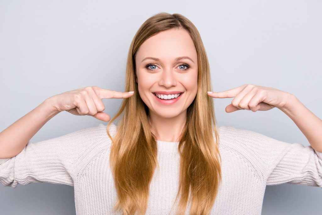 young woman smiling and pointing at her veneers in Simpsonville, SC